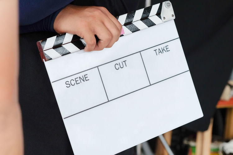 Film Slate, close up image of film production crew holding Film Slate on set Behind The Scenes Filming Studio Behindthescenes Broadcast Broadcasting Clapper Board Clapperboard Close-up Day Event Film Crew Film Industry Film Location Film Production Film Slate Human Body Part Human Hand Indoors  Men One Person Paper People Real People Studio Photography Studio Shot Time Women