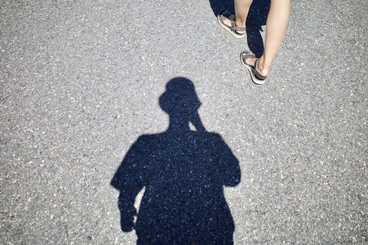 Shadow and low section of people walking on road