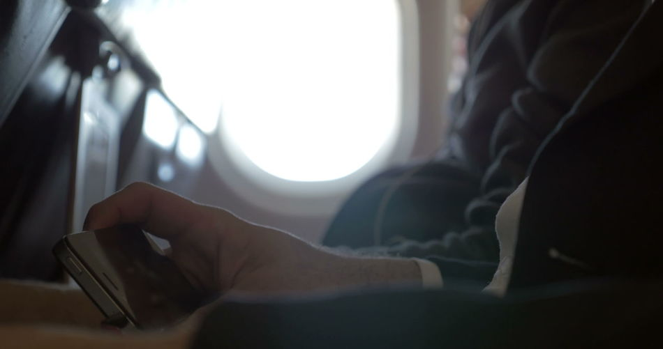Close-up of hand using mobile phone against window