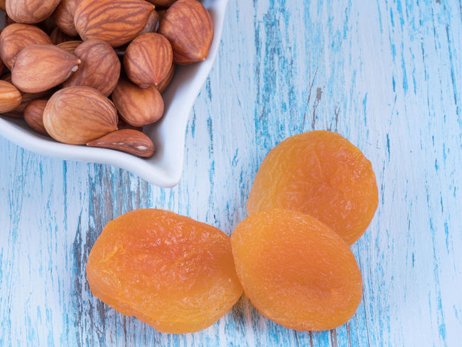 Heap of dried apricots and kernel on wooden background Apricots Close-up Day Food Food And Drink Freshness Healthy Eating High Angle View Indoors  No People Table Wood - Material