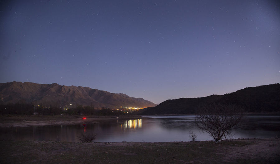 Scenic View Of Lake By Mountains Against Star Field