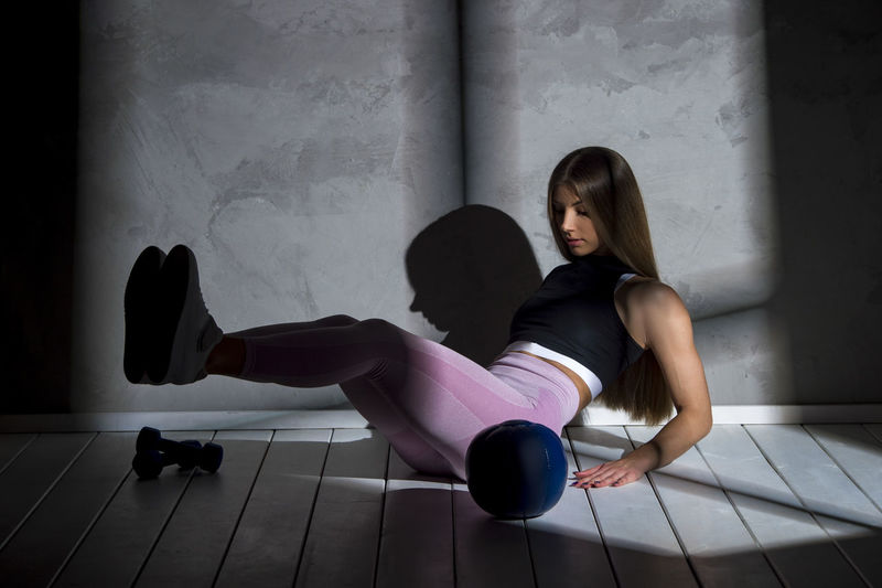 Full length of woman exercising by equipment on floor