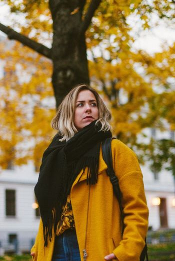 Portrait of beautiful young woman standing against tree during autumn