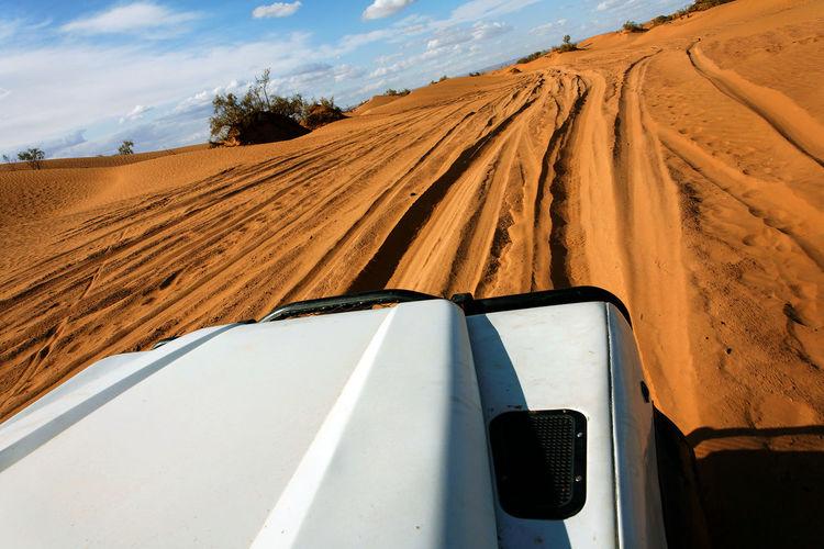 Cropped image of vehicle moving on desert