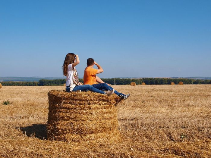 Side view of couple sitting on hay bale against clear sky