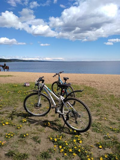 Bicycles on beach by sea against sky
