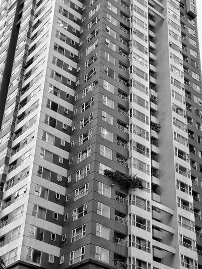 Low angle view of tower buildings in city in black and white