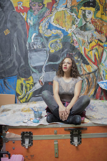 Portrait of young woman sitting on wall