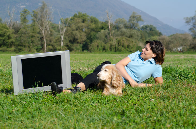 Woman with Her Dog Lying on the Grass and Looking at TV. Adult Creativity Relaxing Animal Animal Themes Canine Casual Clothing Dog Domestic Domestic Animals Field Grass Land Looking At TV Lying Down Nature One Animal One Person One Woman Only Pet Owner Pets Plant Real People Tv Women