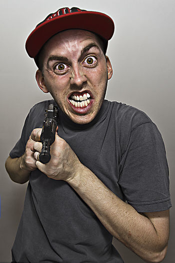 Close-Up Portrait Of Angry Man Holding Gun While Standing Against Gray Background