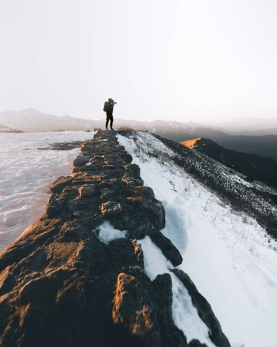 Rear view of man walking on snow covered mountain