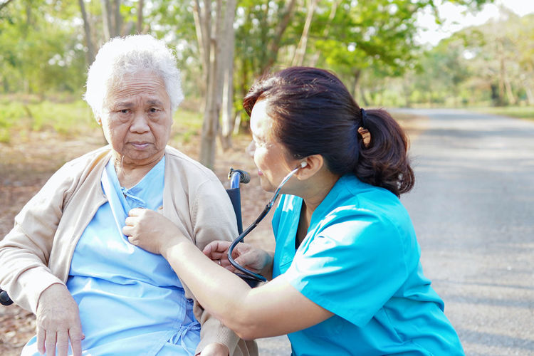 Nurse examining senior female patient sitting on wheelchair at road