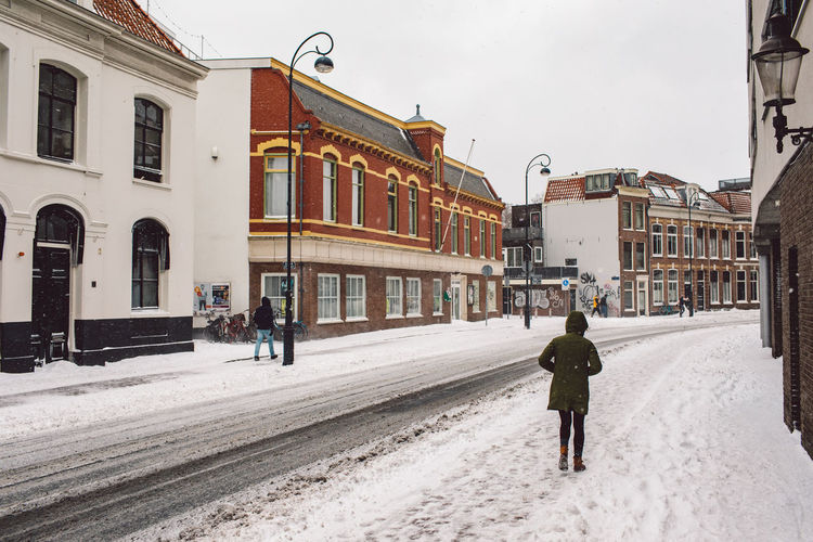 Rear view of woman walking on street in city during winter