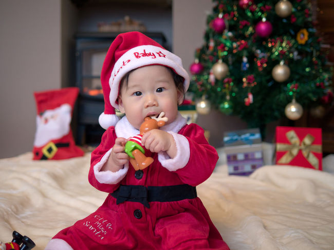 Asian baby girl celebrate her first Christmas Baby Babyhood Bed Celebration Childhood Christmas Christmas Tree Cute Day Home Interior Indoors  Innocence Lifestyles One Person Pacifier Portrait Real People Tree