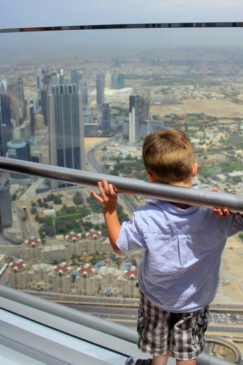 Rear View Of Boy Looking At Cityscape While Standing In Burj Khalifa