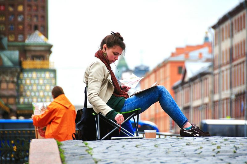 Woman painting while sitting on bridge in city