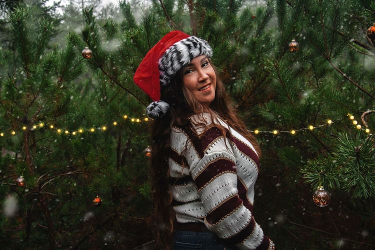 Portrait of smiling woman standing by tree during winter