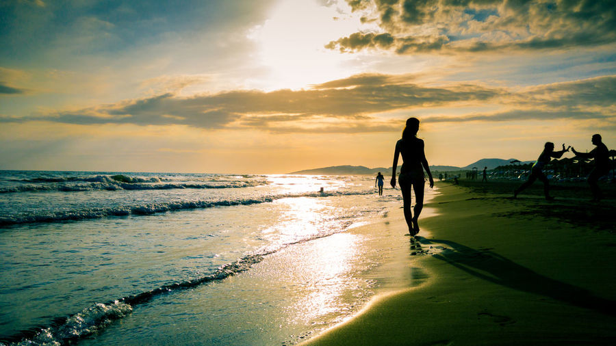 REAR VIEW OF WOMAN WALKING ON BEACH AT SUNSET