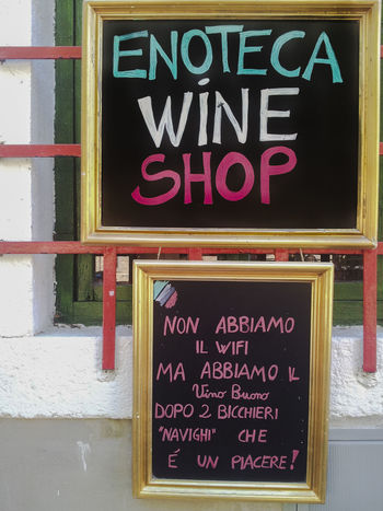 Sign post of wine shop, saying that we do not have wi fi because you can surf with ours good wine Against Apetizer Close-up Communication Day Internet Addiction Make Friends No People Open Sign Outdoors Store Surfing Teasing Text Welcome Sign Western Script Wine Shop Wine Tasting