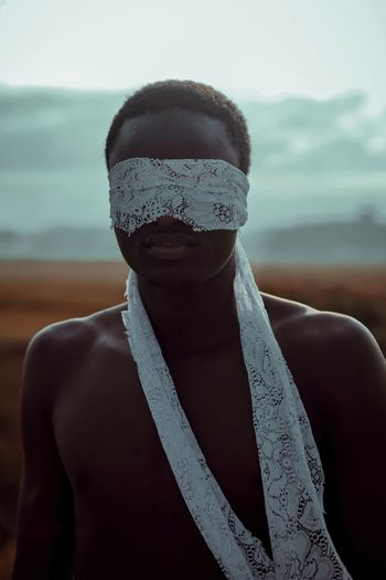 Shirtless young man with blindfold standing outdoors
