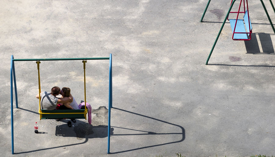 High Angle View Of Couple Kissing On Swing