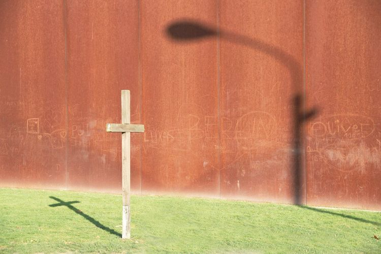 Cross and shadow on the wall of the Berln wall memorial Berlin Wall Architecture Belief Built Structure Cross Cross Shape Day Focus On Foreground Grass Green Color Monument Nature No People Outdoors Plant Religion Shadow Spirituality Sunlight Wall - Building Feature