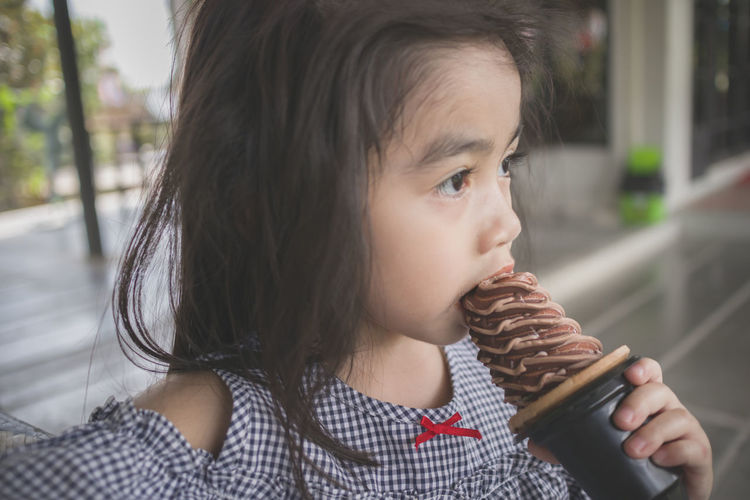 Portrait of cute girl looking away while ice cream