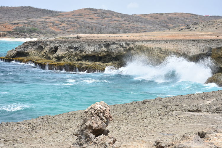 Aruba Beauty In Nature Day Landscape Mountain Natural Bridge  Surf Waves Waves And Rocks Waves Crashing On Rocks Action Power Of Nature Waves Crashing Naturalbridgearuba Nature No People Outdoors Rock - Object Scenics Sky Water Landmark Natural Phenomenon The Great Outdoors - 2017 EyeEm Awards