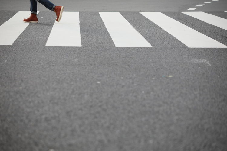 Human Leg Road One Person Street Real People Body Part Low Section Day Human Body Part City Symbol Road Marking Marking Women Sign Transportation Lifestyles Crossing High Angle View Outdoors Human Foot Surface Level Human Limb Crosswalk