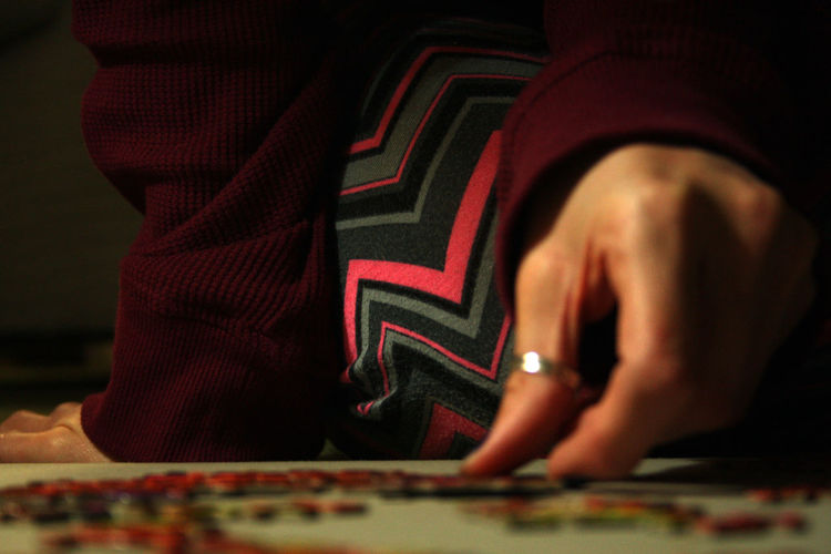 Midsection Of Woman Solving Puzzle On Floor