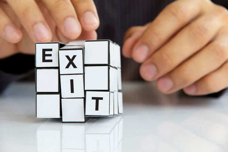 Close-Up Of Hand Holding Puzzle Cube With Exit Text