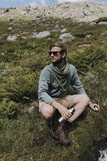 Young man wearing sunglasses sitting on land