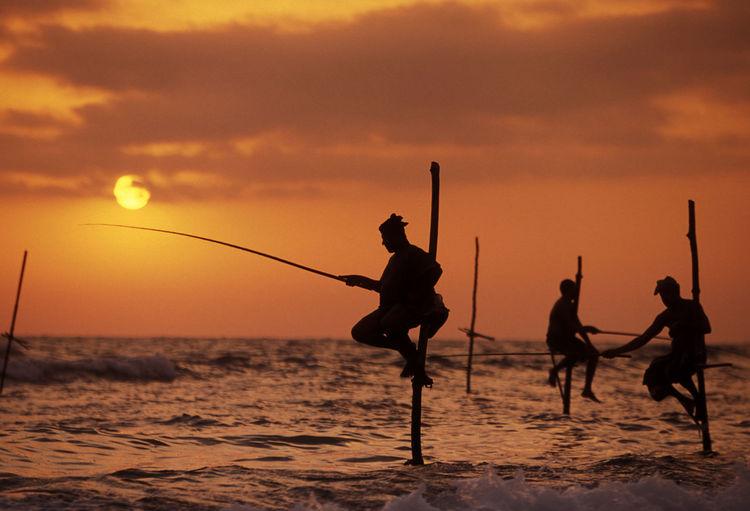 Silhouette Fishermen Stilt Fishing In Sea During Sunset