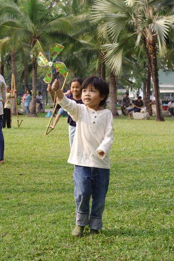 Cute siblings playing with pinwheel at park