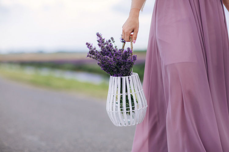 Midsection of woman standing by purple flowering plant