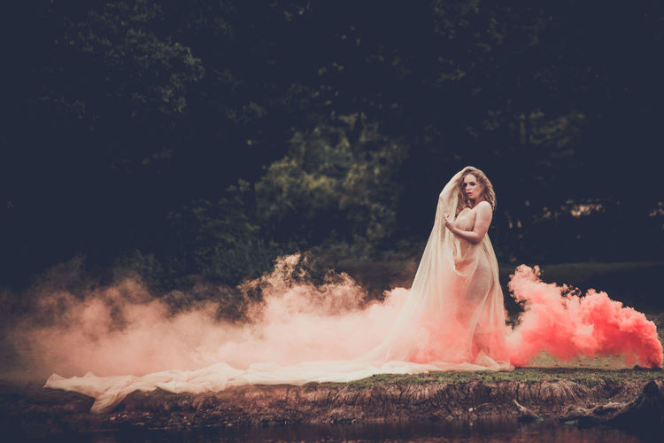 Woman standing by smoke on land against trees
