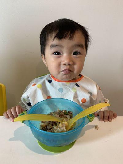 Portrait of cute boy sitting on plate