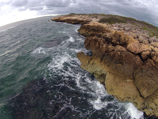 A rocky coastline on the Eastern coast of Puerto Rico. A fisheye lens gives curvature to the horizon and the image simulates the earth from space. A Bird's Eye View Beauty In Nature Cliff Coastline Day Majestic Nature Non-urban Scene Outdoors Remote Rock - Object Rock Formation Scenics Sea Seascape Shore Sky Tourism Travel Destinations Water Wave