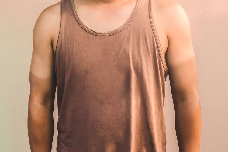 Midsection of man standing against beige background