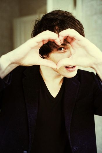 A young man creates a heart shape with hands