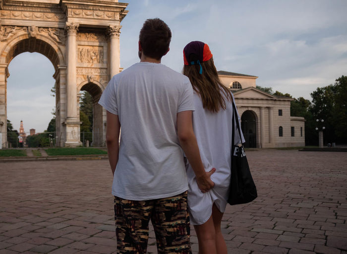 Rear view of man touching girlfriend buttocks while standing against arco della pace