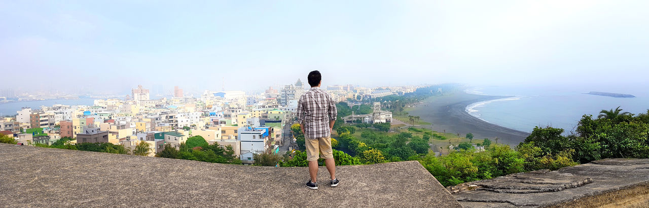 Rear view of man standing by cityscape against sky