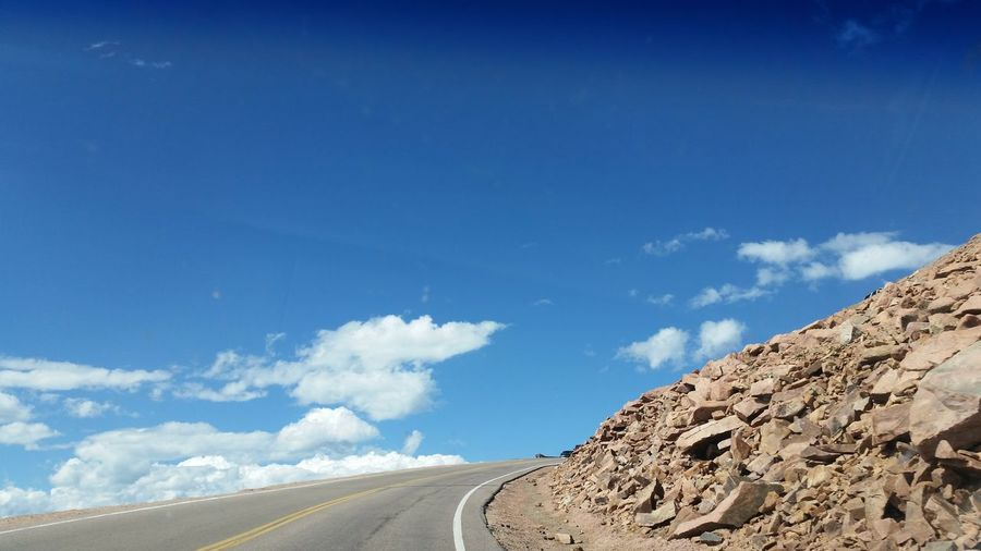 Road Amidst Mountains Against Blue Sky