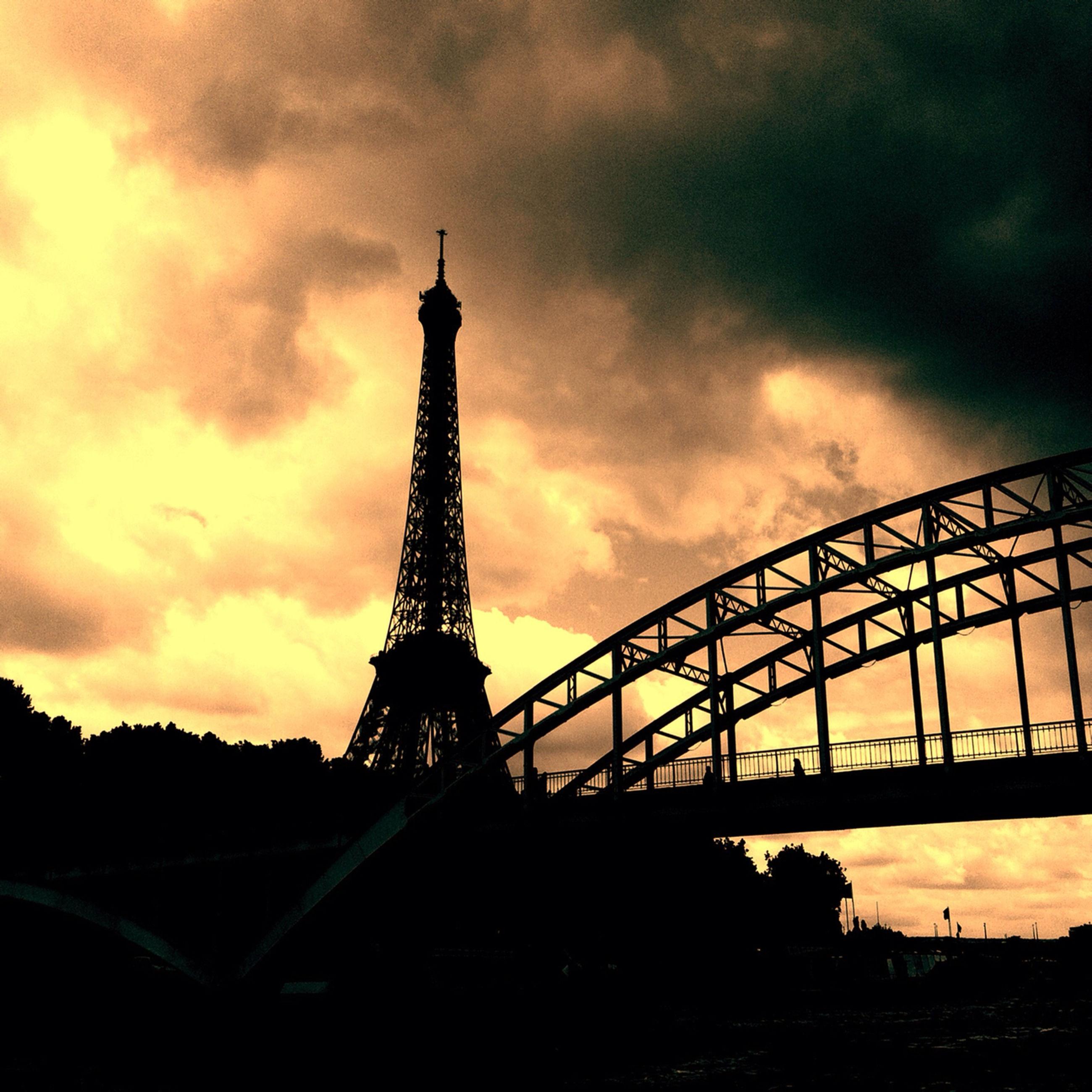 sky, sunset, cloud - sky, built structure, architecture, silhouette, eiffel tower, cloudy, famous place, international landmark, low angle view, travel destinations, orange color, metal, tower, travel, tourism, cloud, dusk, culture