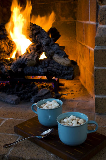 Close-Up Of Marshmallows In Cups By Fireplace