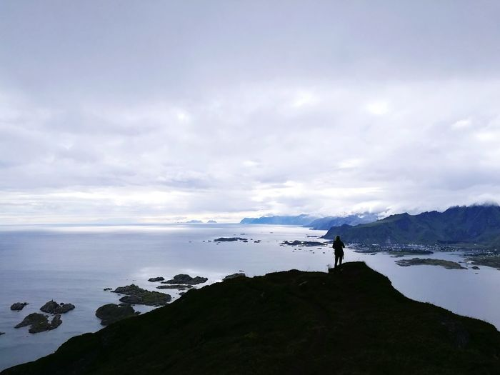 Silhouette person on mountain by sea against sky