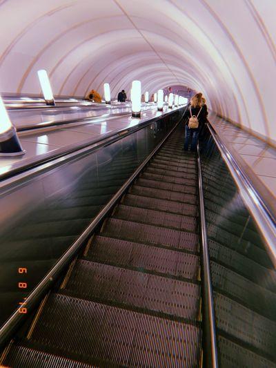 Rear view of man on escalator at subway station