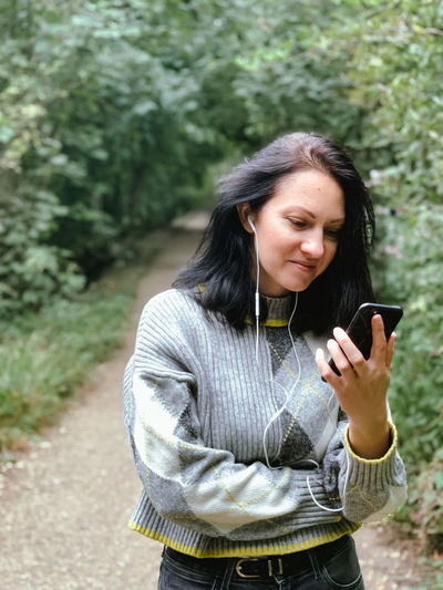Young woman is walking in the park and talking to her friends with using video call.casual lifestyle