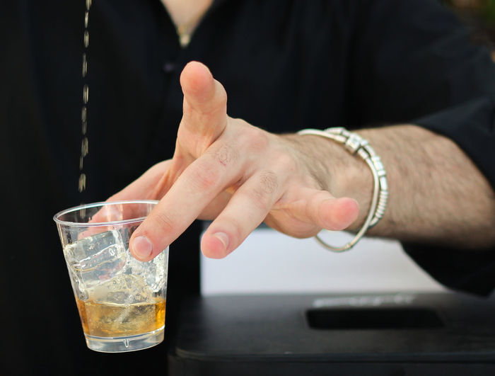 Midsection of man preparing drink