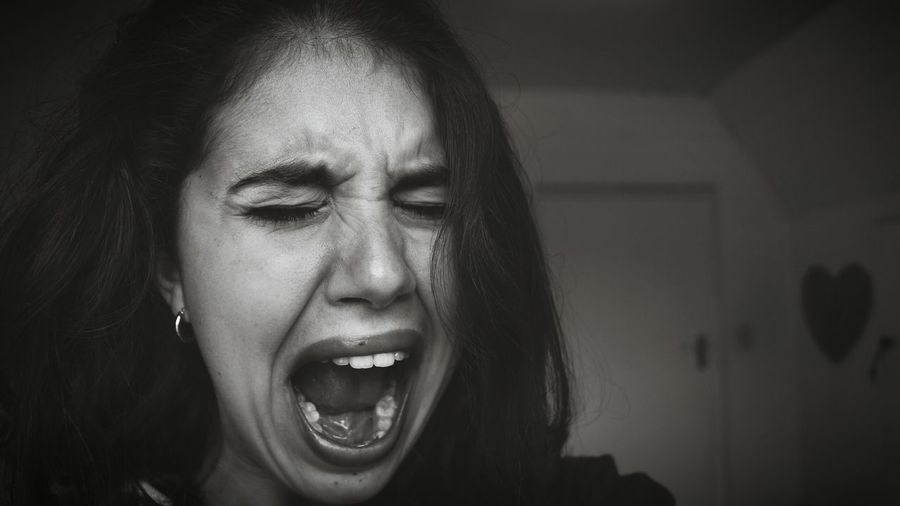 Close-up of woman shouting at home